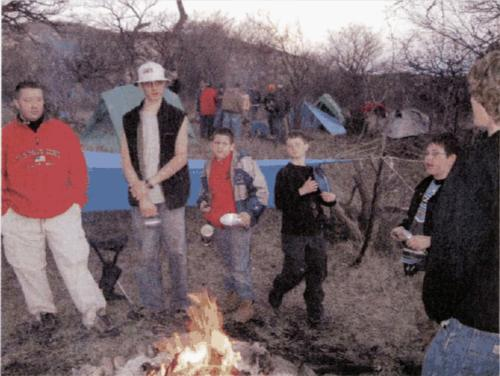 James Spencer, Austin Fielding, Brandon Sena, Adam Jones, A.J. Pagitt, and Will Wood chilling around the campfire.
